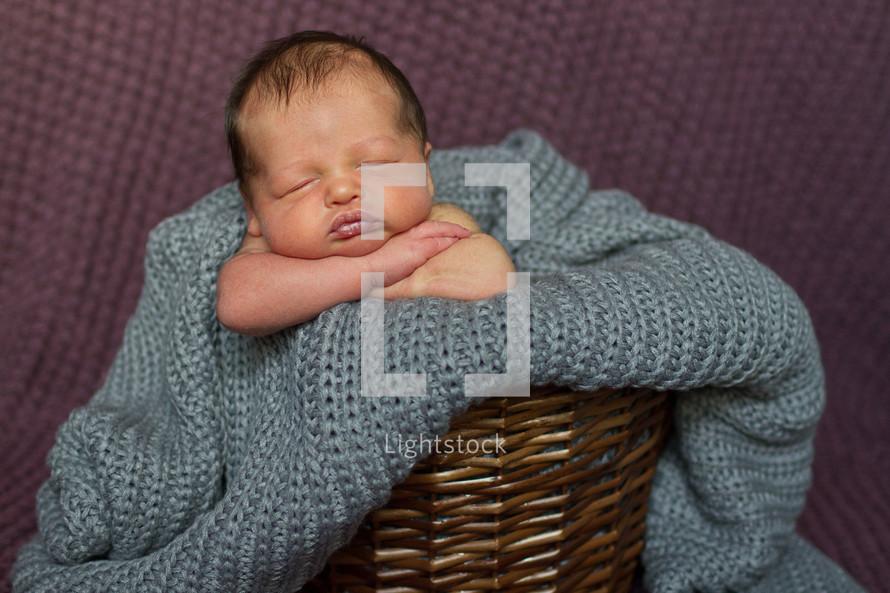 Newborn baby in blanket and wicker basket