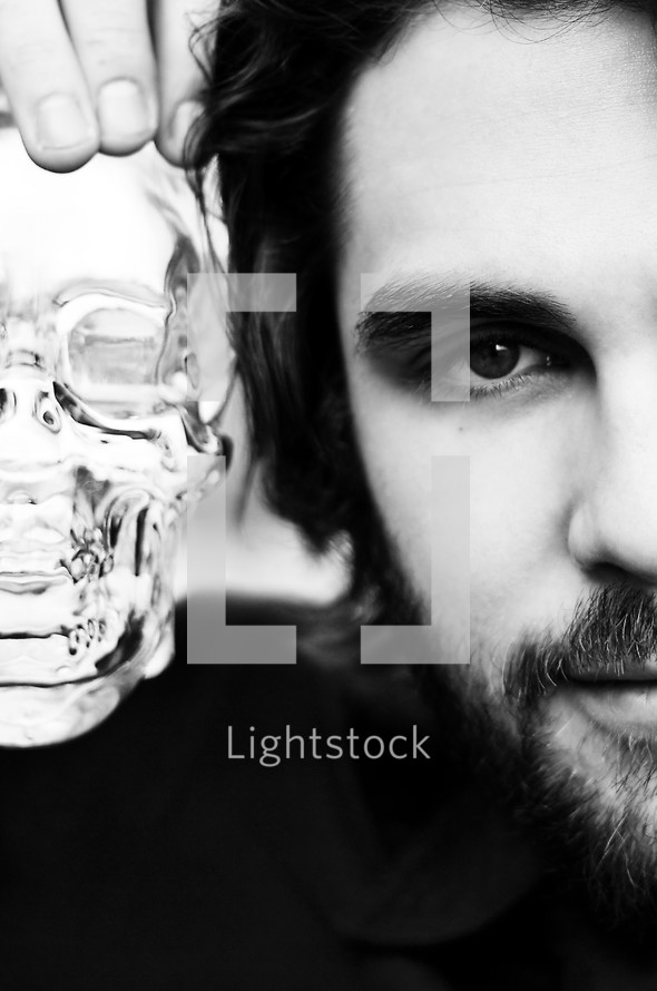 Man holding glass skull beside his face.