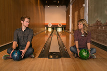 Couple sitting in bowling lanes with balls