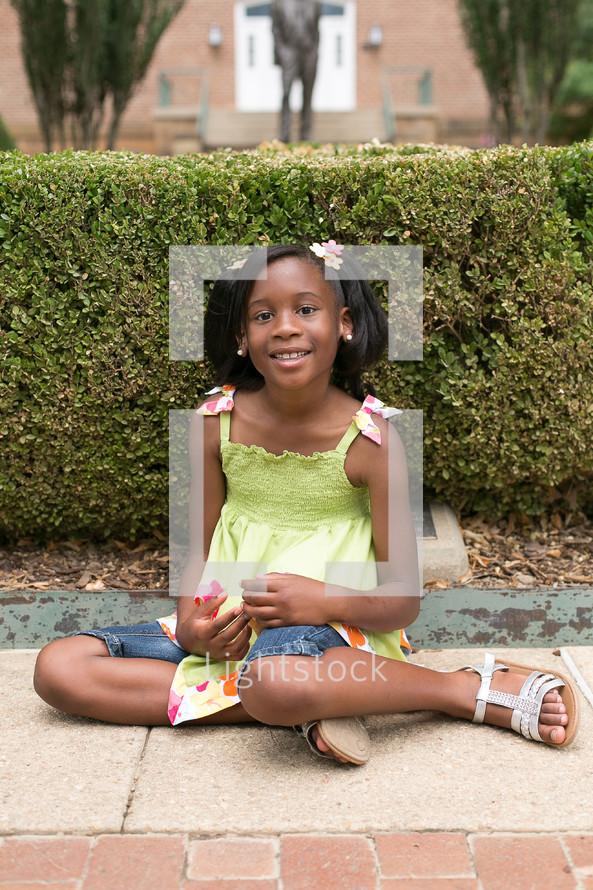 Smiling girl sitting down on sidewalk.