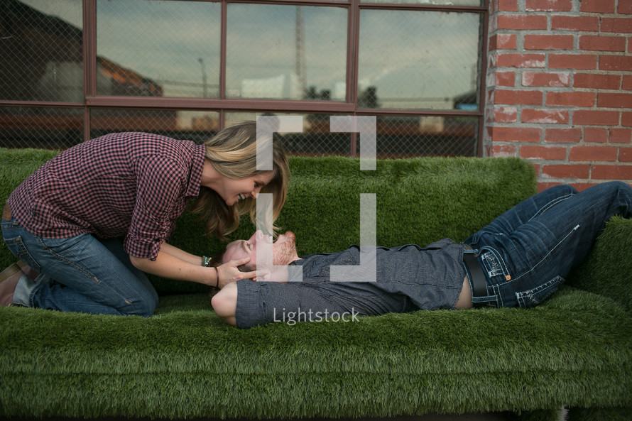 woman leaning over a man on a green fuzzy couch