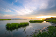 Sunset reflection with marsh grass waterway on the coast