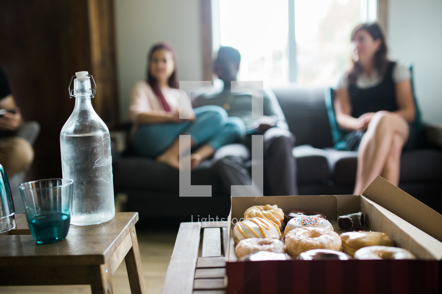 box of donuts and people sitting on a couch