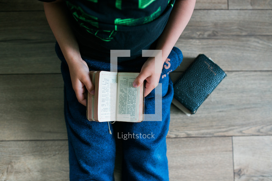 a boy reading from an old Bible