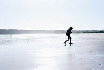 a boy child running on a beach in a coat