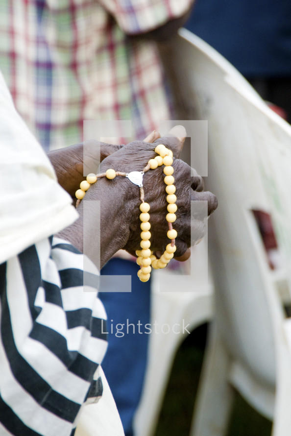 A black woman holds prayer beads