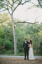 Bride and groom standing on dirt field side of asphalt road with trees in the background.