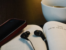 headphones, earbuds, iPhone, open Bible, Bible, The New Testament, title page, coffee, mug