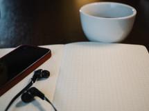 headphones, earbuds, iPhone, open Bible, Bible, journal, graph paper, coffee, mug