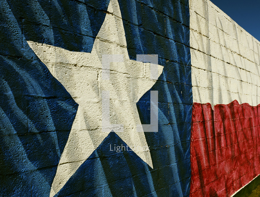 Texas flag mural painted on a brick wall.