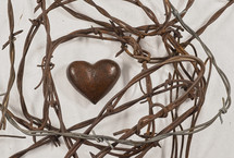 Stone heart surrounded by barbed wire.