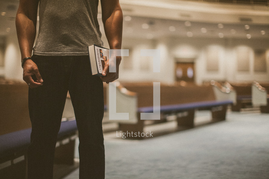 Man standing in front of church pews holding a Bible.