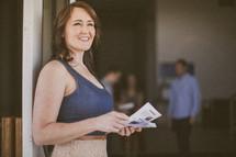 woman handing out church bulletins