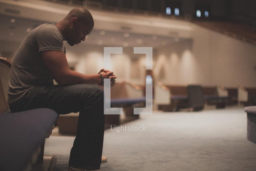 man alone in prayer in an empty church