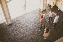 People greeting each other in the lobby of a building.