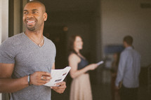 man passing out church bulletins