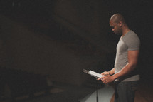 Man reading at a lectern on a stage.