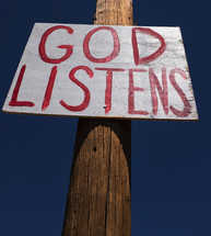"""God Listens"" sign nailed to a telephone post."
