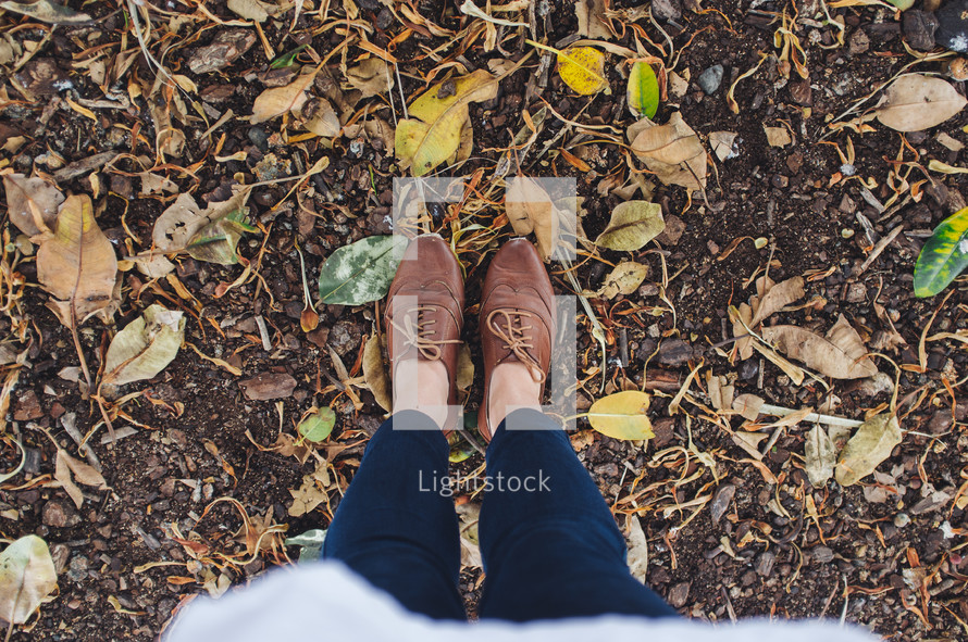 Standing in the dirt with fall leaves.
