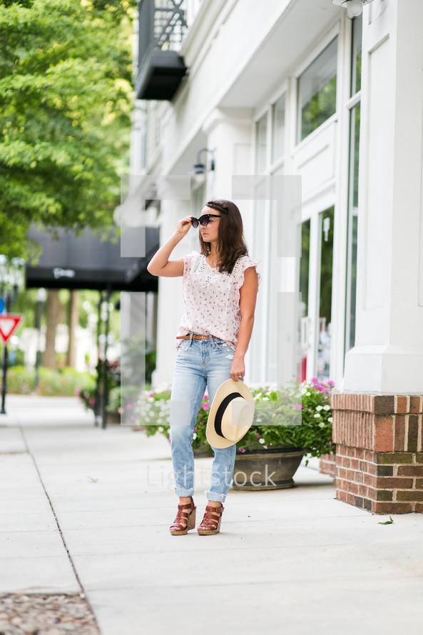 a teen girl standing on a sidewalk