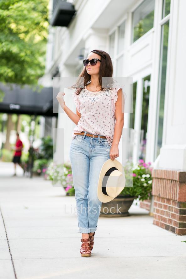 a teen girl holding a hat posing on a sidewalk