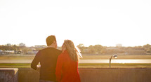 couple close together looking off a balcony