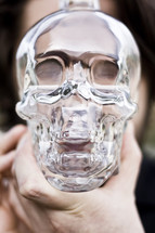 Man holding glass skull in front of face.