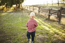 toddler boy walking in a pasture