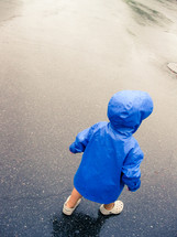 toddler in a raincoat on wet pavement