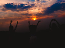 girls with raised hands standing outdoors at sunset