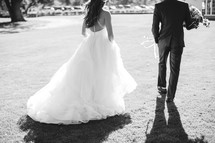 bride and groom walking across a lawn