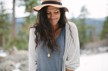 a squinting woman outdoors wearing a hat