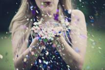 a woman blowing glitter