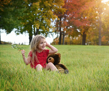 a happy little girl sitting in grass with her teddy bear
