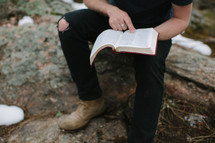 a man sitting on a rock reading a Bible outdoors