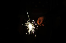 A hand holding a lit sparkler in the dark.