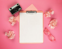 clipboard with white paper and pink items