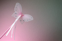 Pink butterfly wand with ribbons and heart shaped jewel head.