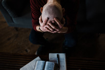 a distressed man praying and reading a Bible for comfort
