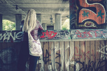 young woman looking over a graffiti covered wall under an overpass