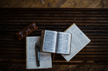 opened Bible and notebooks on a coffee table