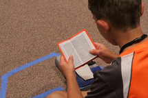 boy child sitting reading a Bible