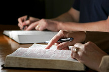 A couple studies the Holy Bible together - Can be during devotional time or with a bible study group.
