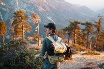 a man backpacking through a mountain forest
