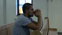 a man kneeling in prayer in church