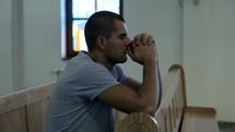 a man kneeling in prayer in church