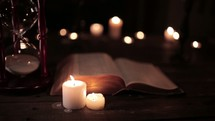 votive candles and flipping pages of a Bible