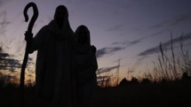 A silhouette of Joseph and a pregnant Mary on the Christmas journey to Bethlehem at night.