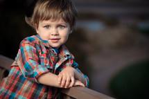 Toddler boy leaning against woodeen rail.