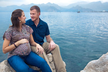 Pregnant woman with man sitting on rock with ocean and moutanins in the background.